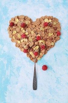 Lepel & hartvorm van gezonde muesli cornflakes op blauw.