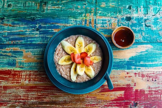 Lepel havermoutpap met banaan en aardbei op de houten achtergrond gezond ontbijt
