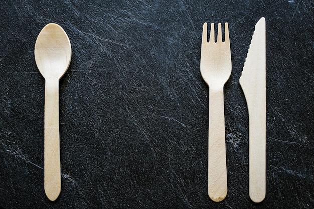 Lepel, mes en vork op een donkere stenen ondergrond