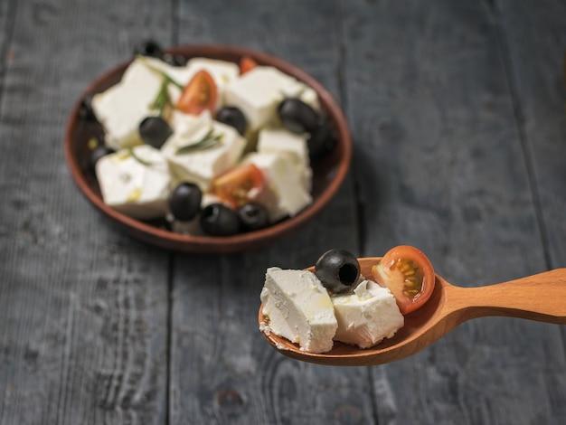 Lepel met feta-kaassalade met tomaten en olijven. salade met kaas en groenten.