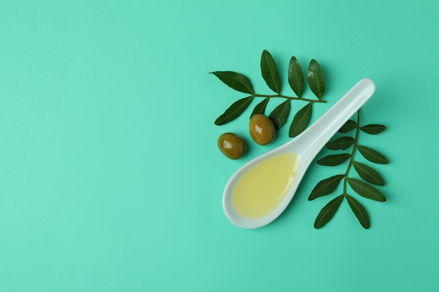 Lepel met olie, olijven en takjes op muntoppervlak