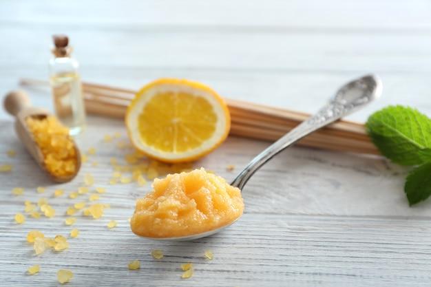 Lepel met oranje scrub, zeezout en muntblad op houten tafel