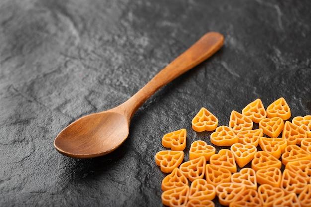 Lepel rauwe hartvormige pasta op zwarte achtergrond.
