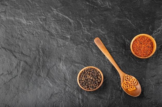 Lepel rauwe pasta en peperkruiden op zwarte achtergrond.