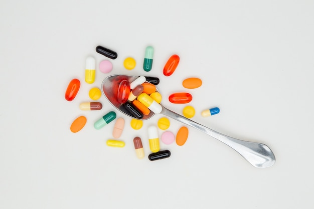 Lepel vol met gekleurde pillen geïsoleerd