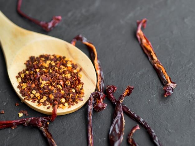Lepel vol met specerijen op zwarte achtergrond