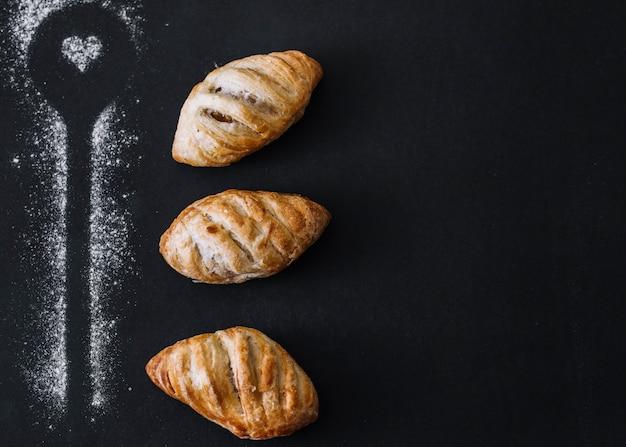 Lepel vorm gemaakt met meel in de buurt van croissants op zwarte achtergrond