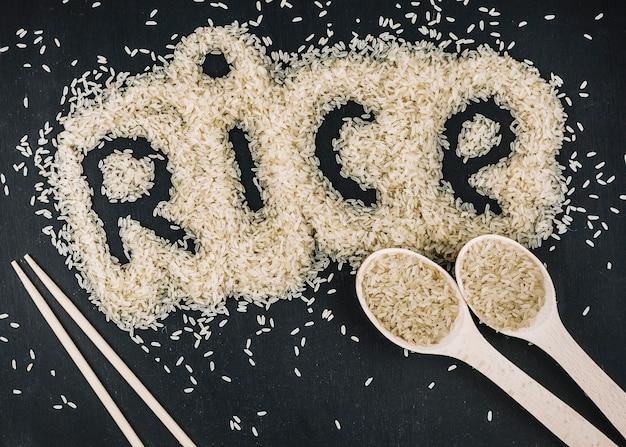 Lepels en eetstokjes in de buurt van rijst schrijven