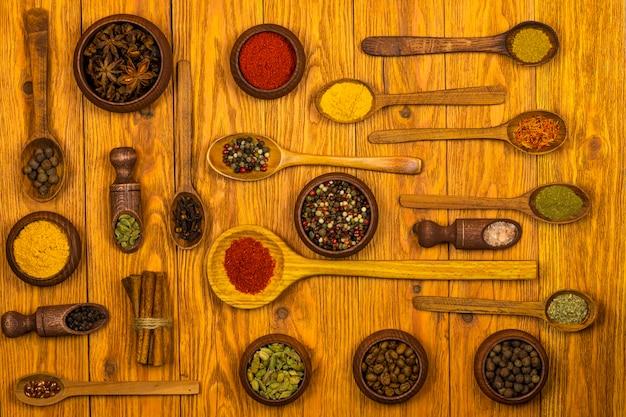 Lepels en kommen gemaakt van hout met een assortiment van kruiden op een lichtbruine houten ondergrond. bovenaanzicht.