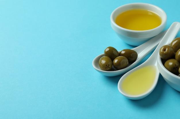 Lepels en kommen met olijven en olie op blauwe ondergrond