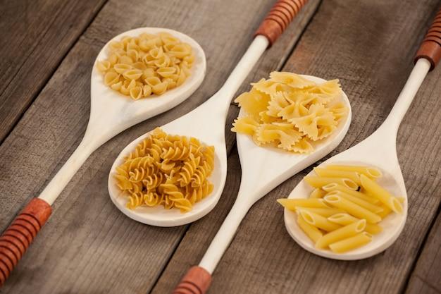 Lepels gevuld met soorten pasta op houten achtergrond