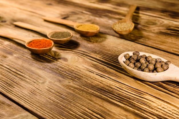 Lepels met de verschillende kruiden op houten tafel