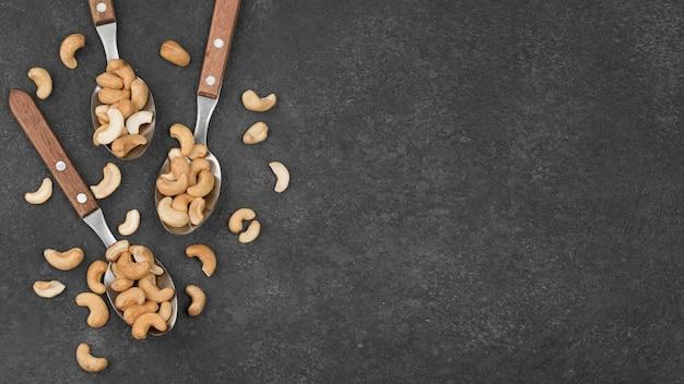Lepels met gezonde rauwe cashewnoten kopiëren ruimte