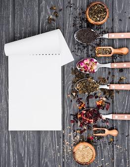 Lepels met kruidenthee naast notebook