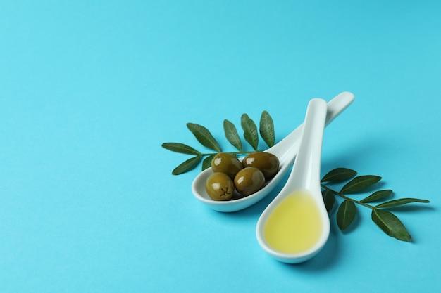 Lepels met olijven en olie, en takjes op blauwe ondergrond