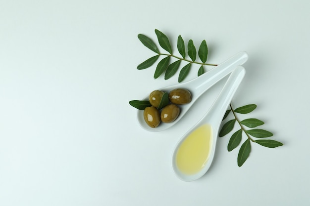 Lepels met olijven en olie, en takjes op wit oppervlak