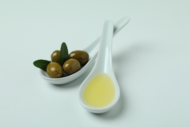 Lepels met olijven en olie op een witte ondergrond