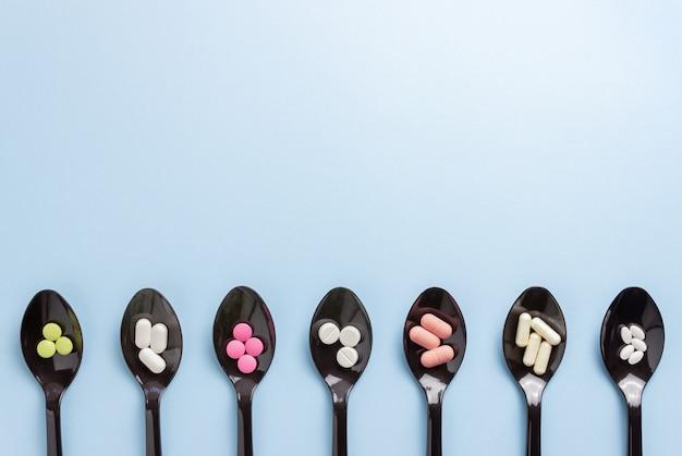 Lepels met pillen op een blauwe tafel. geneesmiddel. medicatie. gezondheid.