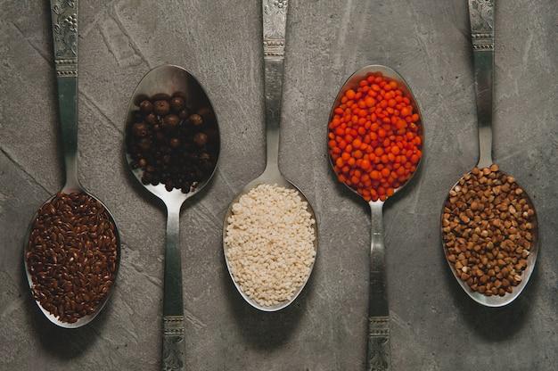 Lepels met verschillende superfoods - lijnzaad, sesam, peper, rode linzen, boekweit op een grijze ondergrond.