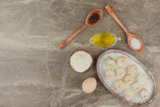 Lepels met zout, peper, olie, ei, bloem en dumplings.