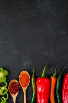 Lepels van specerijen en paprika's op zwarte tafel