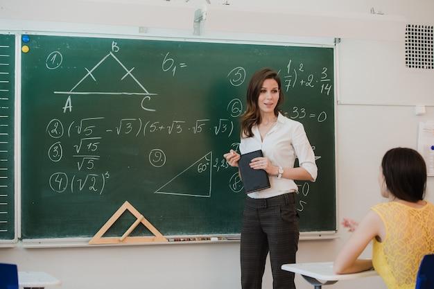 Leraar answering pupils question in klaslokaal