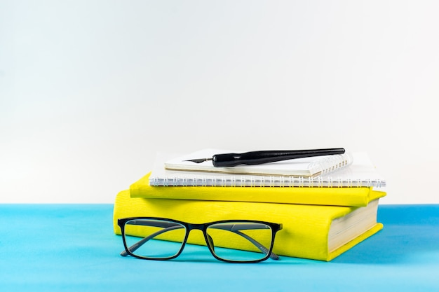Leraar bril, boeken en houten letters op een blauwe tafel. school en leraar dag concept. kopieer ruimte.