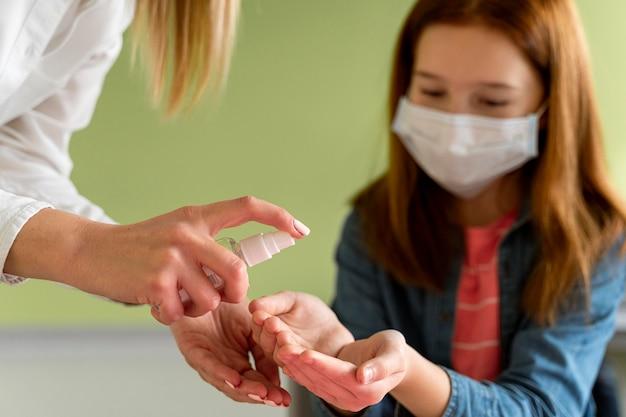 Leraar desinfecteert de handen van het kind in de klas