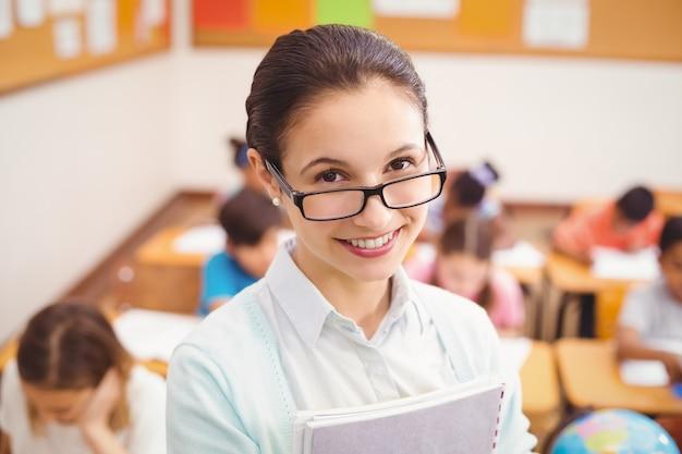 Leraar die bij camera in klaslokaal glimlacht