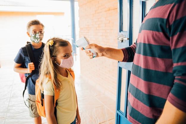 Leraar die de temperatuur van een kind met een thermometer neemt tijdens de covid-pandemie. ze heeft geen koorts, ze is gezond