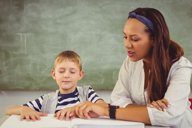 Leraar die een jongen helpt met zijn huiswerk in de klas