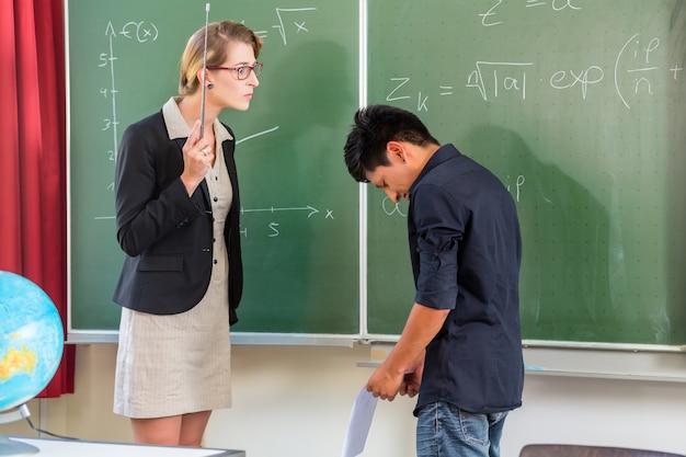 Leraar die een leerling in schoolklasse kritiseert