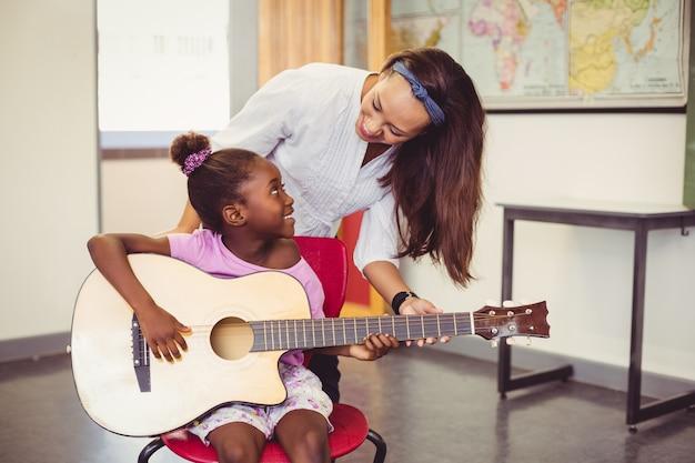 Leraar die een meisje bijstaat om een gitaar in klaslokaal te spelen