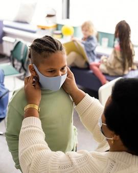 Leraar die een student helpt om een medisch masker op te zetten