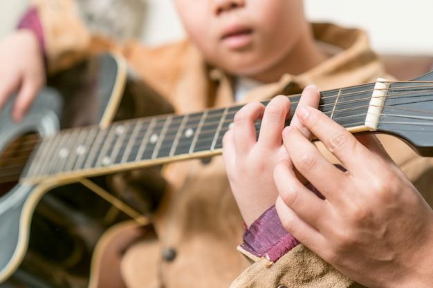 Leraar die gitaarlessen geeft aan leerling in een klaslokaal