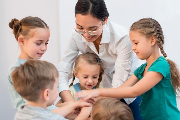 Leraar die haar handen samen met haar studenten voor een spel samenstelt
