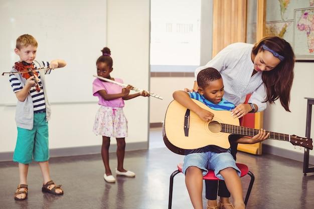Leraar die kinderen bijstaan om een muziekinstrument in klaslokaal te spelen