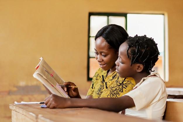 Leraar die kinderen in de klas helpt