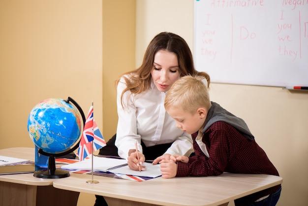 Leraar die mannelijke leerling met het lezen bij bureau helpt.