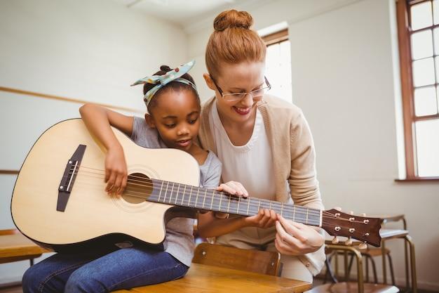 Leraar die meisje onderwijzen om gitaar in klaslokaal te spelen