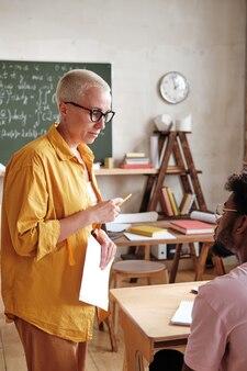 Leraar die met studenten op school werkt