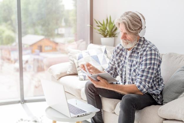 Leraar die notitieboekje dichtbij laptop bekijkt