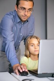Leraar die op middelbare leeftijd taak controleert en zich achter meisje bevindt