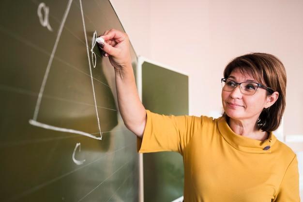 Leraar die op schoolbord schrijft