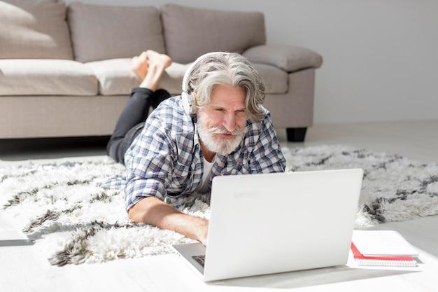 Leraar die op vloer blijft die laptop met behulp van