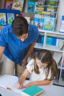 Leraar die schooljong geitje helpen met haar huiswerk in bibliotheek