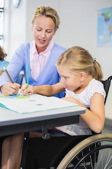 Leraar die schoolmeisje met haar huiswerk in klaslokaal helpt