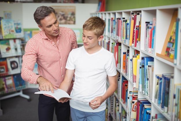 Leraar die student bijstaat bij het lezen van boek in bibliotheek
