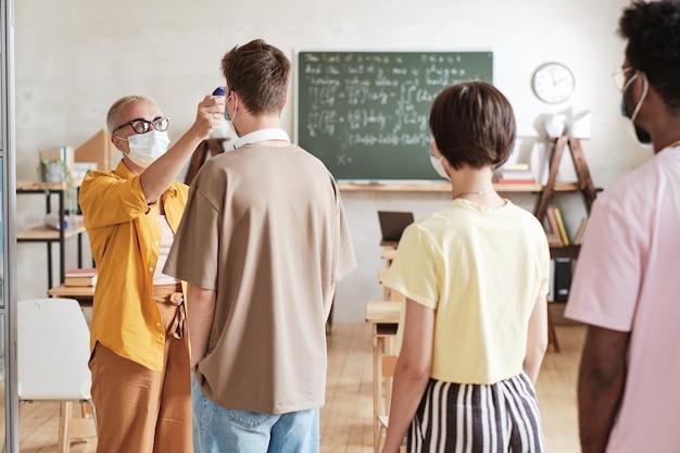 Leraar die studenten vóór les onderzoekt