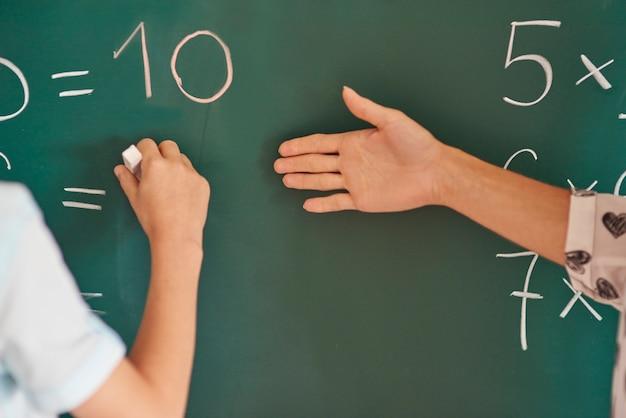 Leraar en haar leerling naast het bord